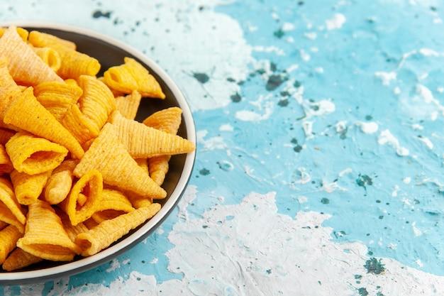 Vooraanzicht kleine pittige chips in plaat op lichtblauw oppervlak