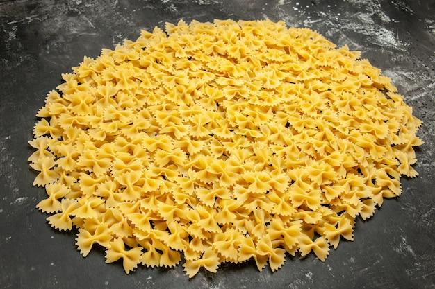 Vooraanzicht kleine rauwe pasta op donker veel deeg eten maaltijd kleur italiaanse pasta foto
