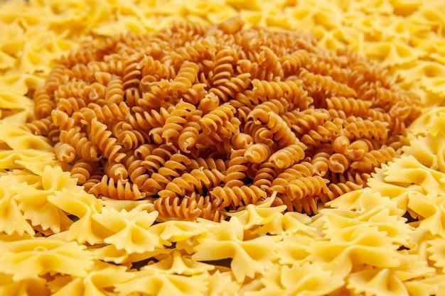 Vooraanzicht kleine rauwe pasta op donkere kleurenfoto veel deeg italiaanse pasta eten maaltijd