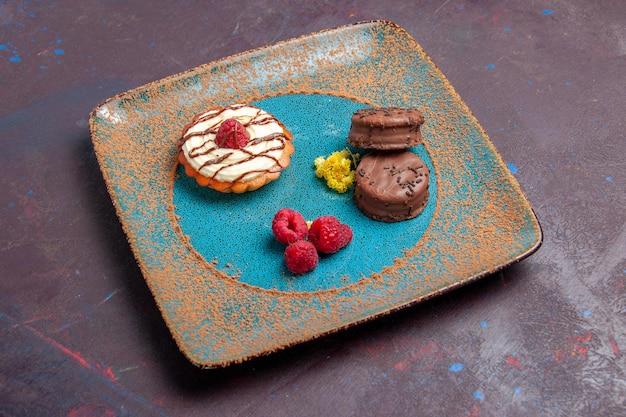 Vooraanzicht kleine romige cake met chocoladekoekjes in plaat op donkere achtergrond biscuit suiker cake zoete taart