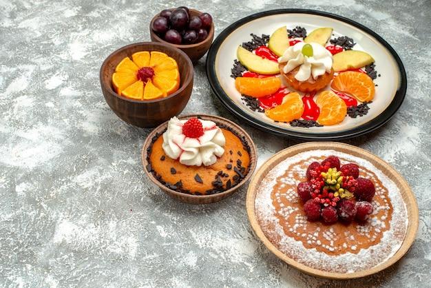 Vooraanzicht kleine romige cake met frambozencake en taart op een witte achtergrond, fruit, zoete koekjes, caketaartsuiker