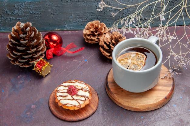 Vooraanzicht kleine romige cake met kopje thee op donkere achtergrond taartkoekje, zoete suikerkoekjescake