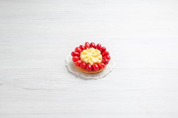 Vooraanzicht kleine romige cake met kornoeljes op een wit de cakedessert van de de kleurenroom van het bureau