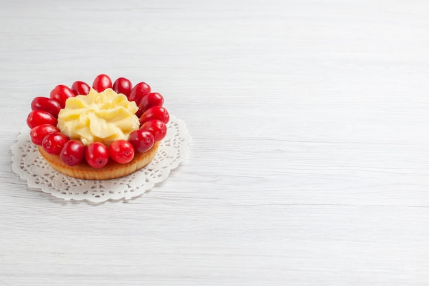 Vooraanzicht kleine romige cake met kornoeljes op een wit dessert van de de kleurcake van het bureaucrème fruit
