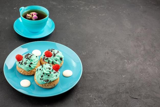 Vooraanzicht kleine romige taarten, heerlijke snoepjes met een kopje thee op de donkere achtergrond, theeroomtaart, biscuitdessertkleur