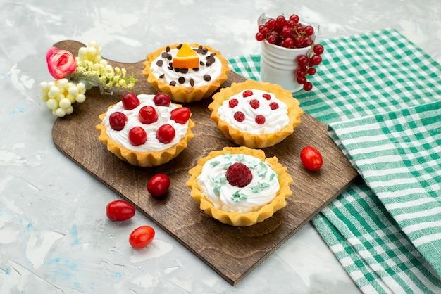 Vooraanzicht kleine slagroomtaartjes met fruit op het lichtgrijze bureau