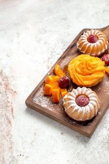 Vooraanzicht kleine taarten perfect dessert voor thee met fruit op witte achtergrond thee taart taart dessert zoete cookie