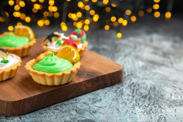 Vooraanzicht kleine taartjes op de kerstversieringen van de snijplank op donkere kerstverlichting