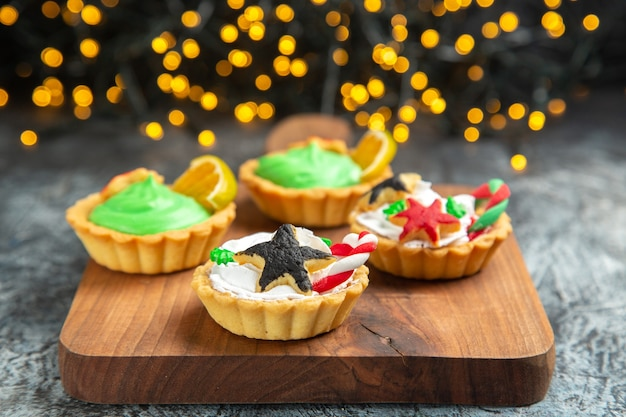 Vooraanzicht kleine taartjes op snijplank op donkere geïsoleerde oppervlak kerstverlichting