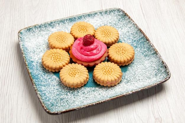 Vooraanzicht kleine zoete koekjes met fruitcake binnen plaat op wit bureau zoete koekjeskoekjescake suikerthee