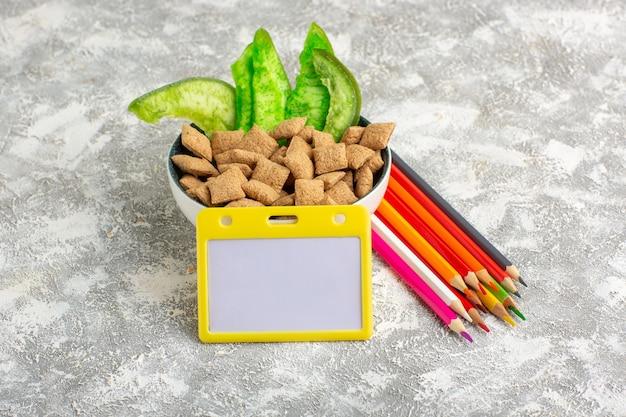 Vooraanzicht kleine zoete kussens met potloden op wit oppervlak