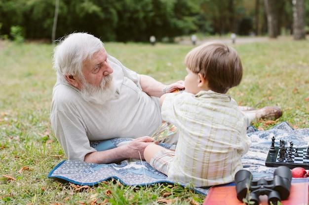Vooraanzicht kleinzoon en opa op picknick
