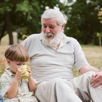 Vooraanzicht kleinzoon met opa thee drinken