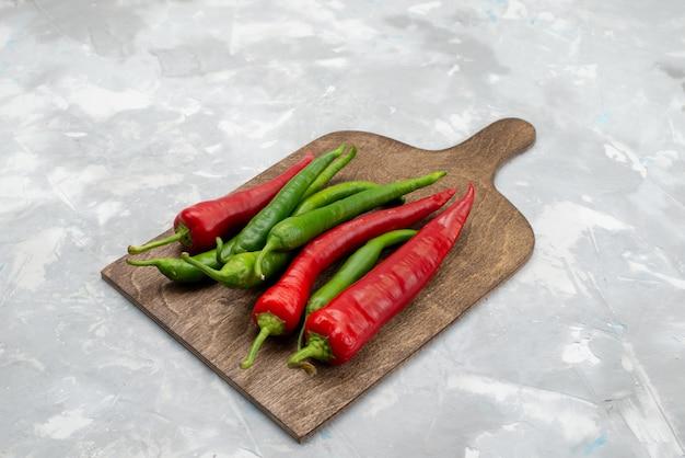 Vooraanzicht kleurde kruidige paprika's groen en rood op het lichte hete plantaardige ingrediënt van het bureaukruid