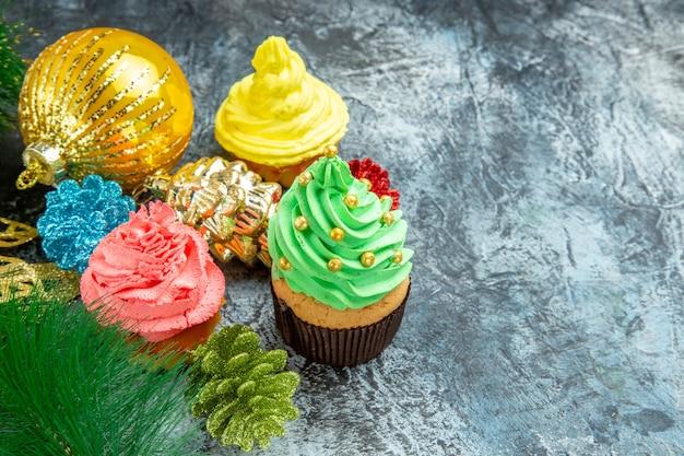 Vooraanzicht kleurrijke cupcakes kerst ornamenten op grijze achtergrond vrije plaats