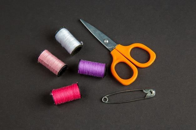 Vooraanzicht kleurrijke draden met een schaar op donkere ondergrond duisternis kleding naaien brei kleur vrouw naai pin foto