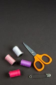 Vooraanzicht kleurrijke draden met een schaar op donkere ondergrond duisternis kleding naaien brei vrouw naaien pin fotokleur