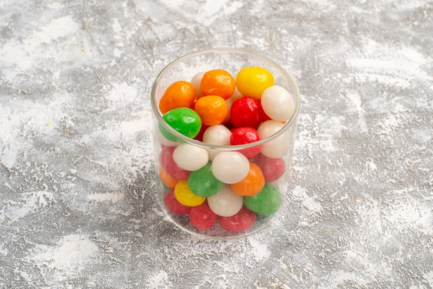 Vooraanzicht kleurrijke snoepjes in klein glas op witte ruimte