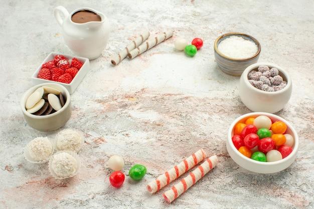 Vooraanzicht kleurrijke snoepjes met koekjes op witte achtergrond biscuit zoete cake cookie