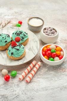 Vooraanzicht kleurrijke snoepjes met slagroomtaarten op wit bureaukoekje, zoete cakekoekje