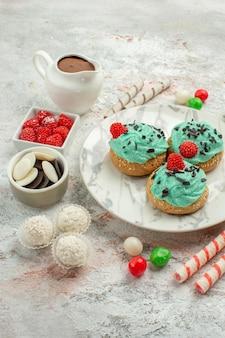 Vooraanzicht kleurrijke snoepjes met slagroomtaarten op witte achtergrond biscuit zoete cake cookie sugar