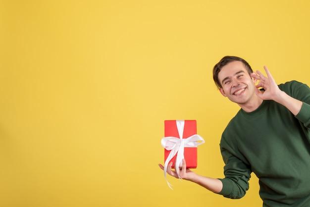 Vooraanzicht knappe jonge man met cadeau maken okey teken op geel