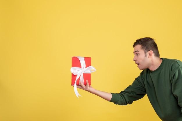 Vooraanzicht knappe jonge man met geschenk op geel