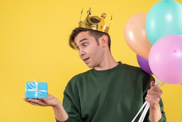 Vooraanzicht knappe jongeman met kroon houden ballonnen kijken geschenk op geel