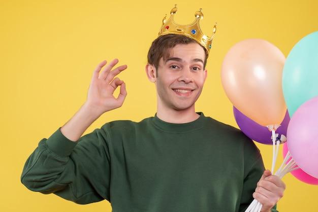 Vooraanzicht knappe jongeman met kroon houden ballonnen ok teken maken op geel