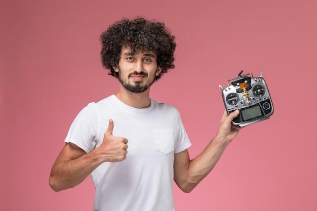 Vooraanzicht knappe man duimen opgevend aan radiocontroller van elektronische robot