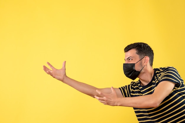 Vooraanzicht knappe man in zwart masker probeert iets te bereiken op gele geïsoleerde achtergrond