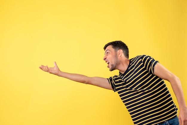 Vooraanzicht knappe man in zwart-wit gestreept t-shirt probeert iets te vangen op gele geïsoleerde achtergrond
