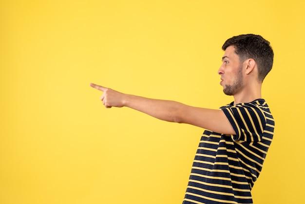 Vooraanzicht knappe man in zwart-wit gestreepte t-shirt gele geïsoleerde achtergrond