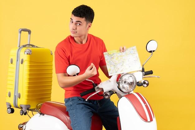 Vooraanzicht knappe man op bromfiets met kaart op geel