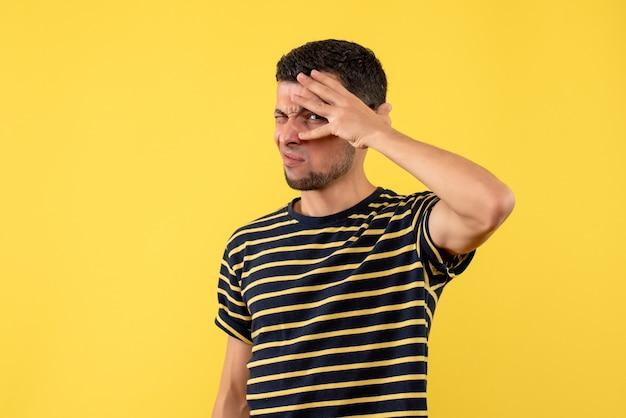 Vooraanzicht knipperde - ogen jonge man in zwart-wit gestreept t-shirt op gele geïsoleerde achtergrond
