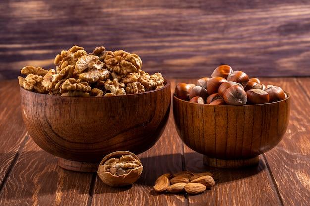 Vooraanzicht kom met inshell hazelnoten met een kom van walnoten en amandelen op tafel