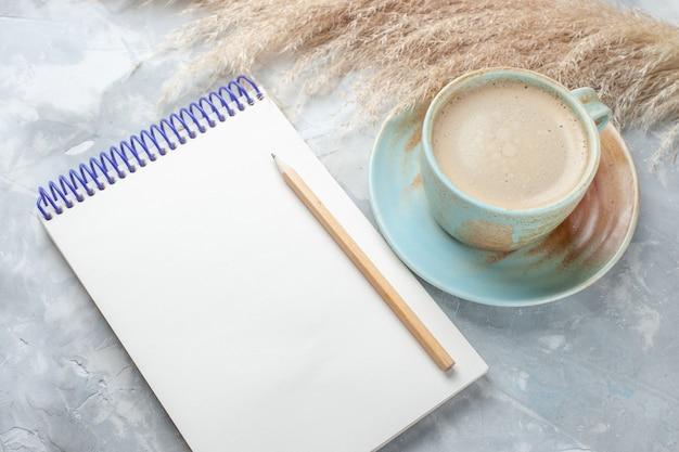 Vooraanzicht kopje koffie met melk in beker samen met blocnote op het witte bureau drinkt koffiemelk bureaukleur
