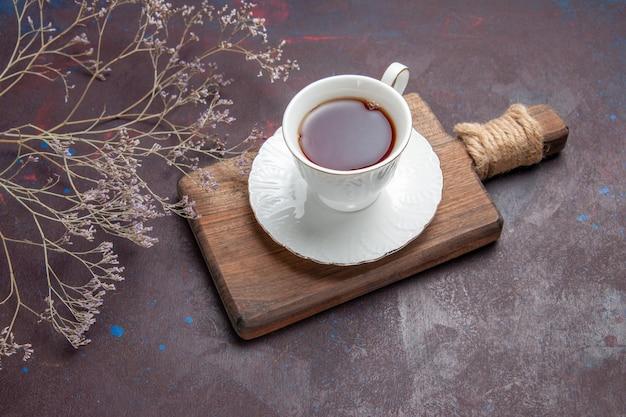 Vooraanzicht kopje thee in glazen beker met bord op de donkere ruimte