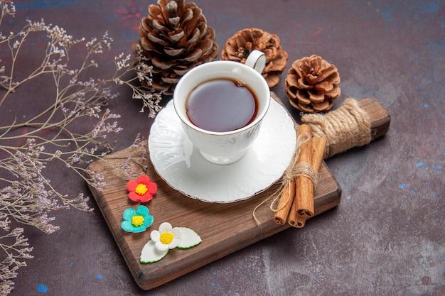 Vooraanzicht kopje thee in glazen beker met bord op donkere bureau thee drinken kleur duisternis ceremonie