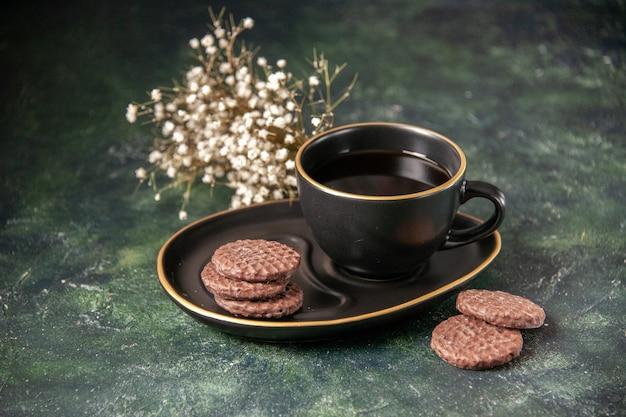 Vooraanzicht kopje thee in zwarte kop en plaat met koekjes op donkere ondergrond kleur suiker glas ontbijt dessert cookie-ceremonie