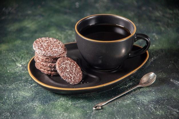 Vooraanzicht kopje thee in zwarte kop en plaat met koekjes op donkere ondergrond suiker ceremonie glas ontbijt dessert kleur cake