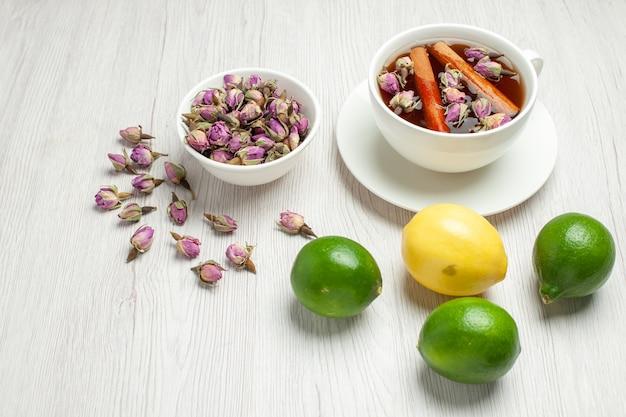 Vooraanzicht kopje thee met bloemen en citroenen op wit bureau thee fruit citrus kleur Gratis Foto