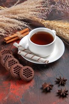 Vooraanzicht kopje thee met chocokoekjes op donkere het koekjesthee van het lijstkoekje