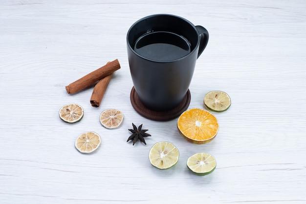 Vooraanzicht kopje thee met citroen en kaneel op licht bureau