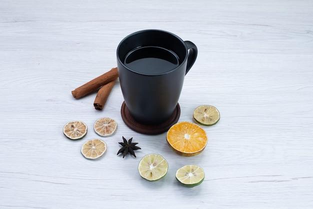 Vooraanzicht kopje thee met citroen en kaneel op wit