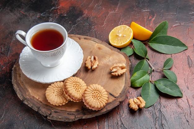 Vooraanzicht kopje thee met citroen en koekjes op donkere achtergrond