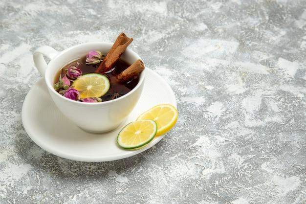 Vooraanzicht kopje thee met citroen op wit oppervlak thee drinkt hete zoete suiker ontbijt