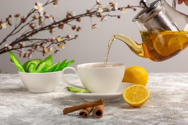 Vooraanzicht kopje thee met citroenen en kaneel op het lichtwitte oppervlak