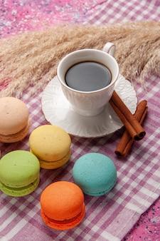Vooraanzicht kopje thee met kaneel en franse macarons op de roze van het het koekjeskoekje van de bureaucake zoete suiker