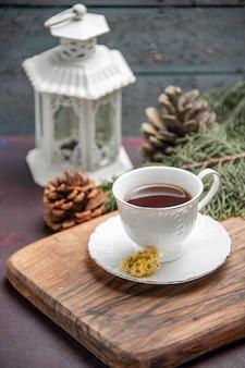 Vooraanzicht kopje thee met kegels op donkere ruimte